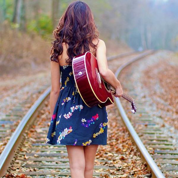 عکس دختر با گیتار در حال راه رفتن